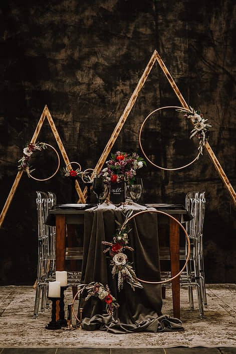 alternative wedding backdrop with acrylic chairs and black backdrop and floral hoops with white anemone and red ranunculus and white pieris and clematis and triangle archways and a wood table