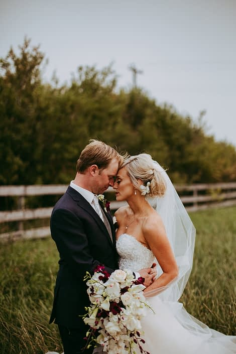 bride and groom in a summer wheat field in a alberta farm wedding holding a bridal bouquet of white and burgundy flowers including burgundy dendrobium and cymbidium orchids