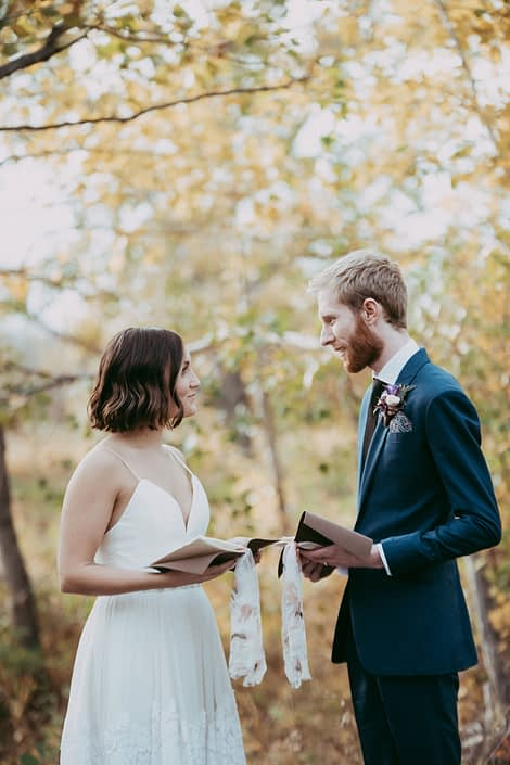 bride and groom with vow books in front of autumn trees