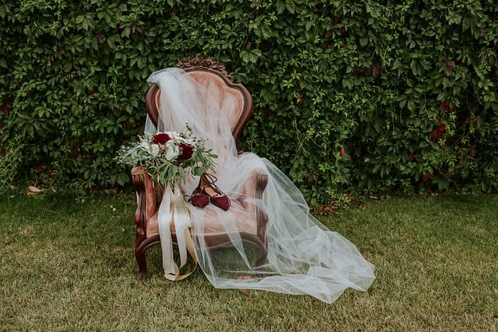 Antique dusty rose chair with bride;s cathedral veil, burgundy shoes and burgundy dahlia, quicksand rose and ivory rose bridal bouquet