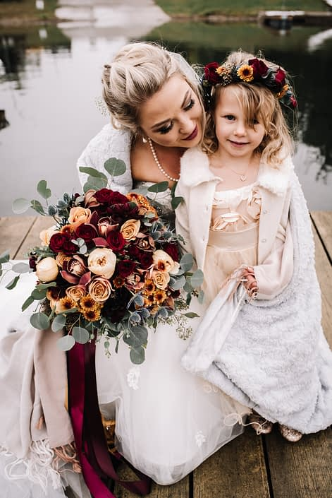 bride and flowergirl in white for a rustic autumn wedding on a lake front holding a bridal bouquet of mustard yellow garden roses, burgundy spray roses and peach roses with santini chrysanthemums and silk trailing ribbons and a flowercorwn