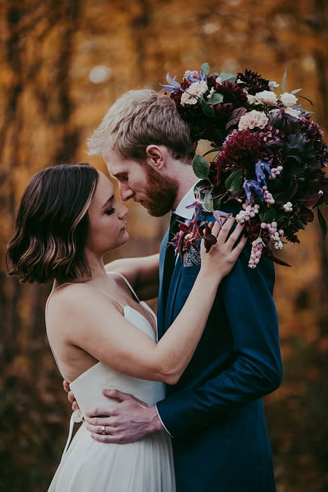 bride in white dress holding a bridal bouquet with burgundy hydrangea and amaranthus ad blush roses and carnations and groom in navy suit with boutonniere