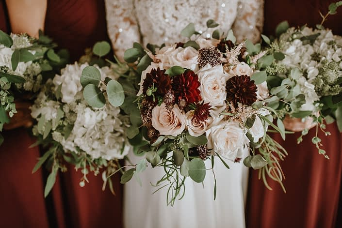 bridal bouquet of burgundy dahlia, white ohara garden roses, blush quicksand roses and eucalyptus and bridesmaid bouquets of white hydrangea and astrantia