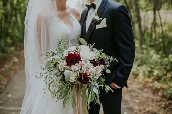 bride with cathedral length veil and groom in navy tux holding a bridal bouquet designedwith burgundy dahlua, quicksand roses and white roses, and astrantia with eucalyptus greenery