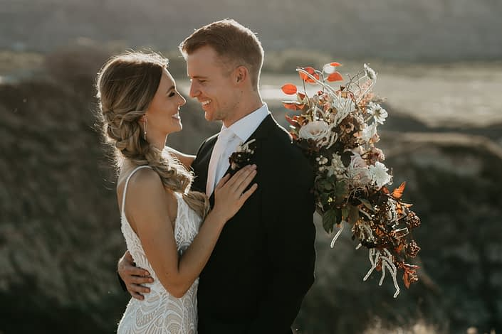 bride and groom at sunset in the drumheller badlands with a bridal bouquet designed with roses, and burgundy greenery