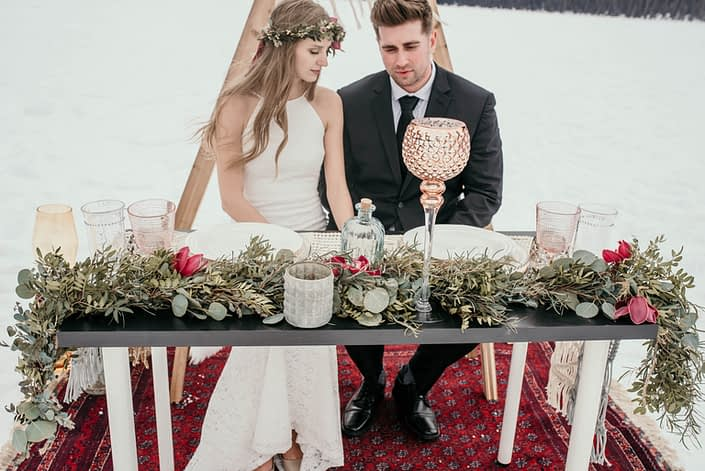 winter photoshoot at lake louise with a greenery garland with burgundy accents placed along the sweetheart table