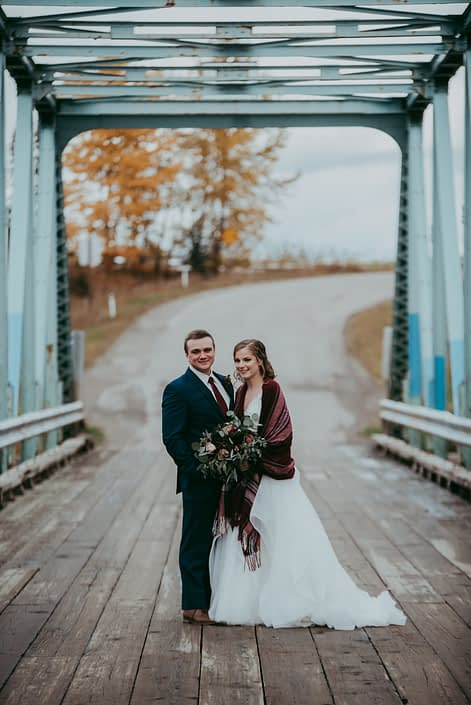 bride and groom on rustic bridge with plaid shawl groom in blue suit and red tie and bridal bouquet with red roses burgundy dahlias and navy viburnum berries and mixed eucalyptus in fall