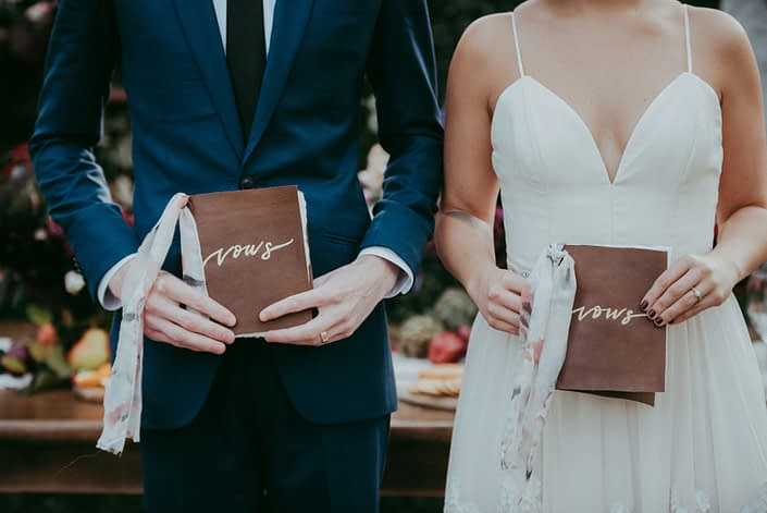 Bride in truvelle wedding dress and groom in navy suit holding leather and silk ribbon bound vow books