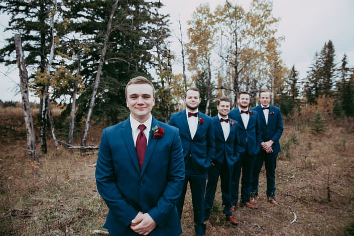 groom and groomsmen in navy suits with red bow ties and red spray rose boutonniere in line on a fall day in a forest