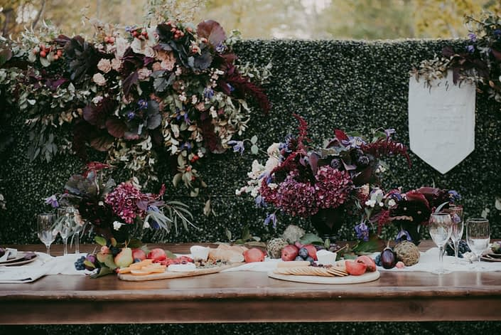 Box wood backdrop with fresh floral accents and menu banner with harvest table and floral designs and charcuterie boards