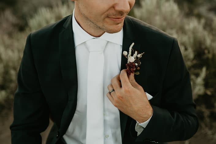 Groom holding a boutonniere designed with rubus berries and white amranthus