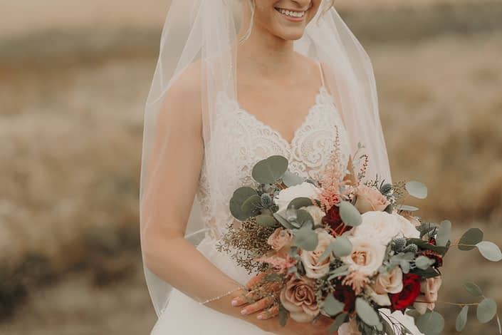 loose and romantic bridal bouquet with red roses and quicksand roses and white o'hara garden roses and pink astilbe and navy eryngium and mixed eucalyptus