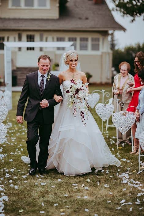 bride and grooms at farnhouse wedding in alberta summer walking f=down the aisle with white rose petals and white dendrobium orchids, burgundy dendrobium orchids and white calla lilies
