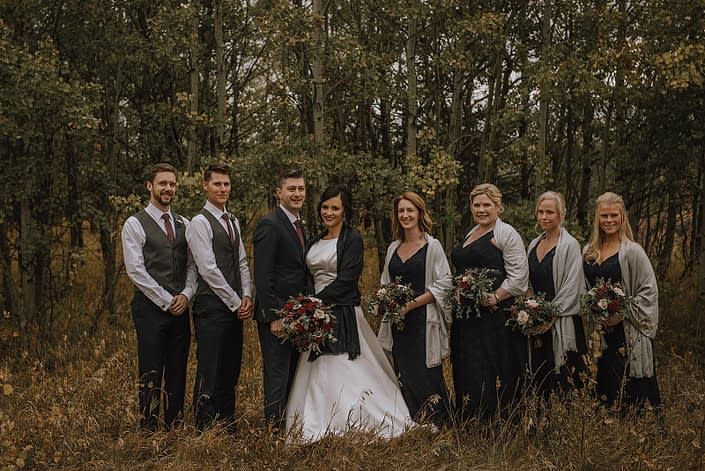 bridal party photo with bridesmaids in grey shawls and bridal bouquets designed with burgundy and navy flowers