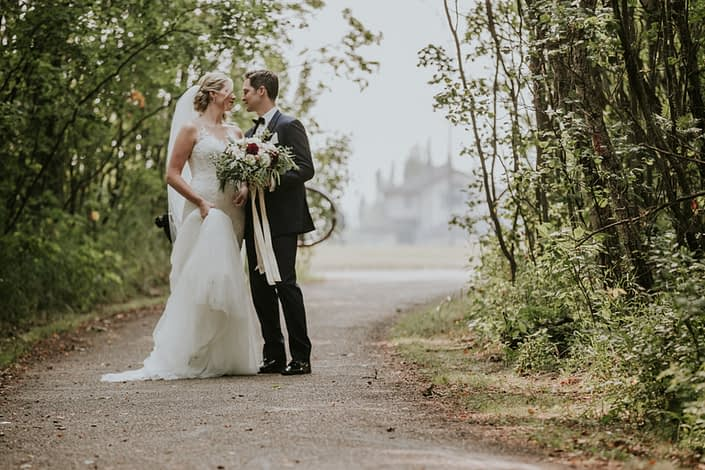 bride and groom on path in the summer with a wedding dress and veil holding a bridal bouquet of eucalyptus and ivory spray roses and burgundy dahia