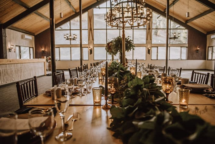 rustic ski lodge long table with mixed greenery garland and tall centerpieces on top of gold candelabras at canyon ski resort in Red Deer alberta