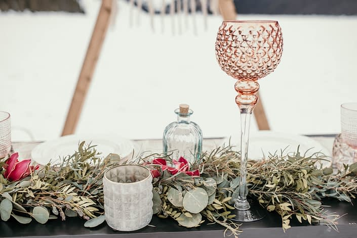 sweetheart table detail shot in winter with fresh eucalyptus garland and burgundy cymbidium orchid accents