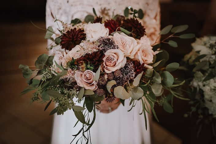 close up of bridal bouquet designed with eucalyptus and burgundy dahlia, blush quicksand roses, plaum scabiosa, burgundy astrantia and pale pink astilbe