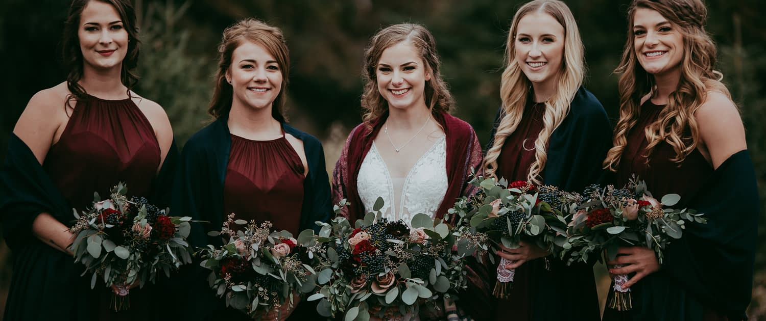 bridal party picture with burgundy bridesmaid dresses and green shawls and bride with plaid shawl and bouquets with red roses burgundy dahlias navy viburnum berries and mixed eucalyptus greenery against forest backdrop in alberta
