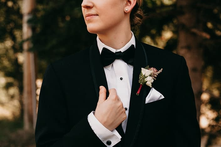 bride in black tuxedo with white spray rose boutonniere and burgundy silk ribbon wrap