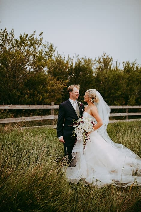 bride and groom in alberta summer wheat field holding a cascade bridal bouquet of white dendrobium orchids and burgundy dendrobium and cymbidium orchids