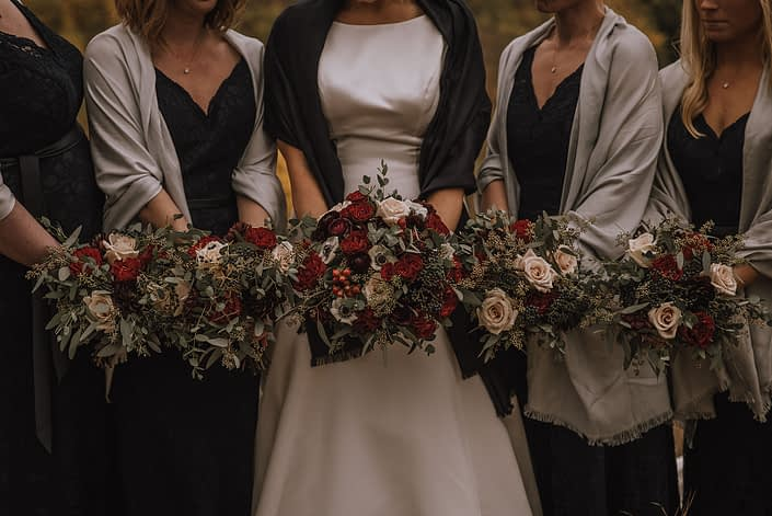 autumn bridal party in black dresses with bride and bridesmaid bouquets designed with ivory sahara roses red hearts garden roses and deep burgundy ranunculus ad accented with eucalyptus greenery