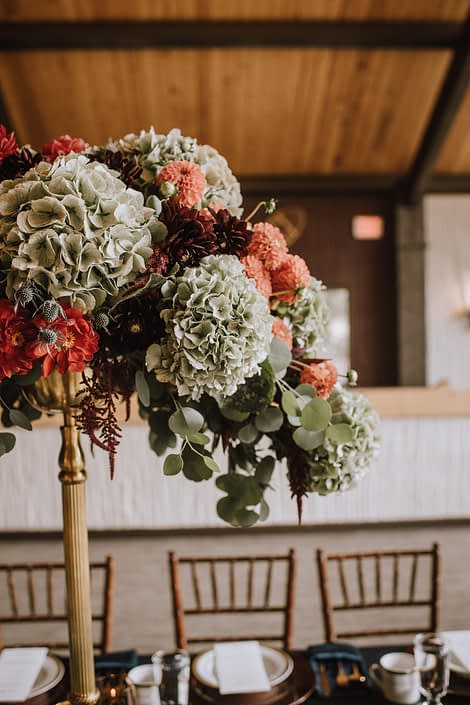 A stunning centerpiece designed atop a gold candleabra designed with hydrangea and burnt orange dahlia