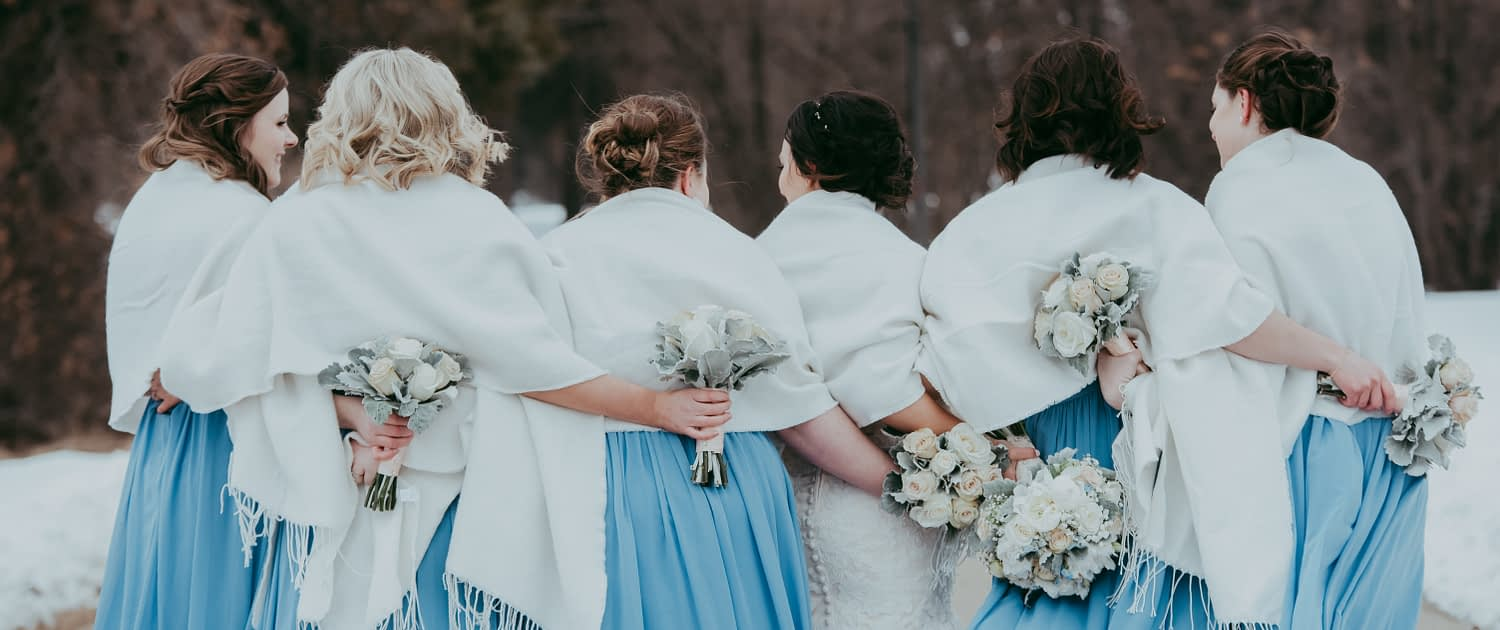 sky blue bridesmaid dresses in a winter wedding with white and grey bouquets