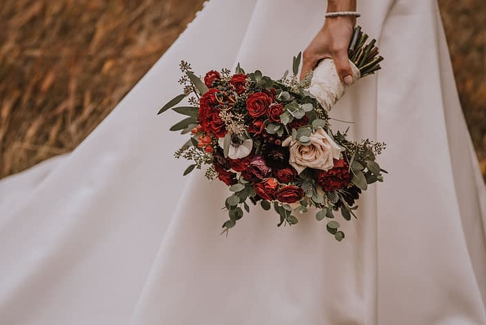 bride with pearl bracelet holding a lace wrapped burgundy and ivory bridal bouquet of roses and ranunculus