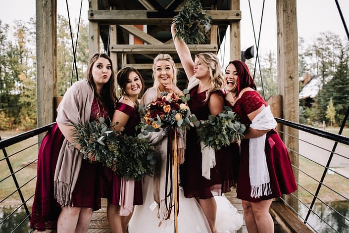 Bride and bridesmaids in burgundy short dresses with white shawls and eucalyptus greenery bouquets bride has a bouquet with silk trailing ribbons in burgundy, navy and mustard yellow and flowers in mustard yellow and burnt orange