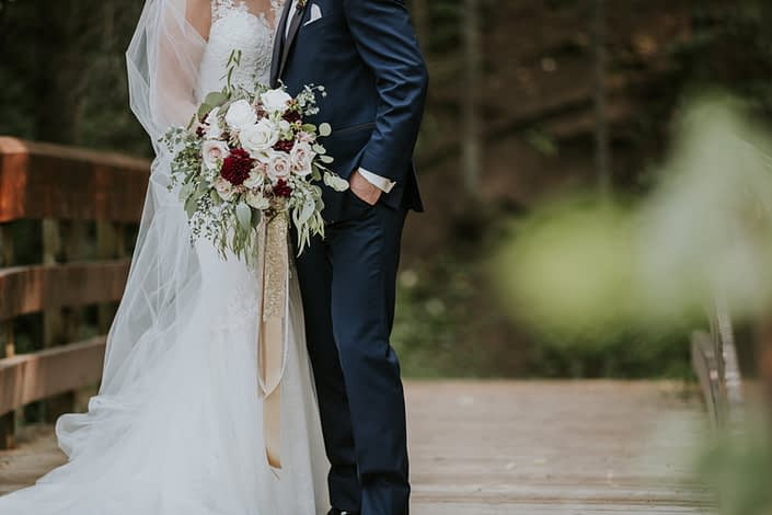 close up photo of bride and groom holding a bouquet designed with eucalyptus and burgundy dahlia and blush roses and white roses with trailing gold and blush ribbons and groom in a navy suit