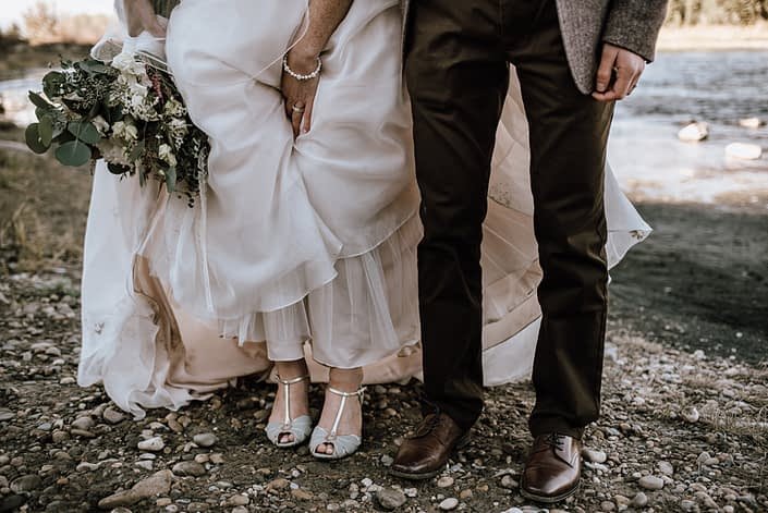 photograph of bride and grooms shoes at the wedding with greenery bridal bouquet