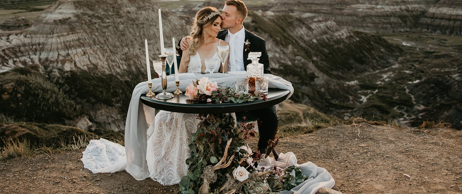 sunset in the badlands photoshoot overlooking the hoodoos with bride and groom and floral accents
