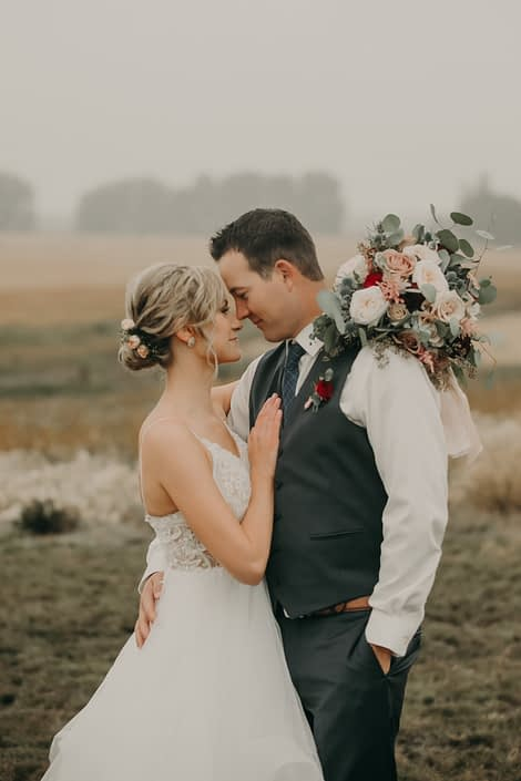 bride and groom portrait with hair flowers with pink spray roses and groom in grey suit with red spray rose boutonniere and bouquet with white o'hara garden roses and pink astilbe and quicksand roses and eucalyptus