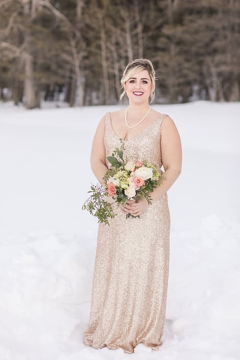 winter bridesmaid in blush sequin dress with bouquet of roses, ranunculus and helleborus