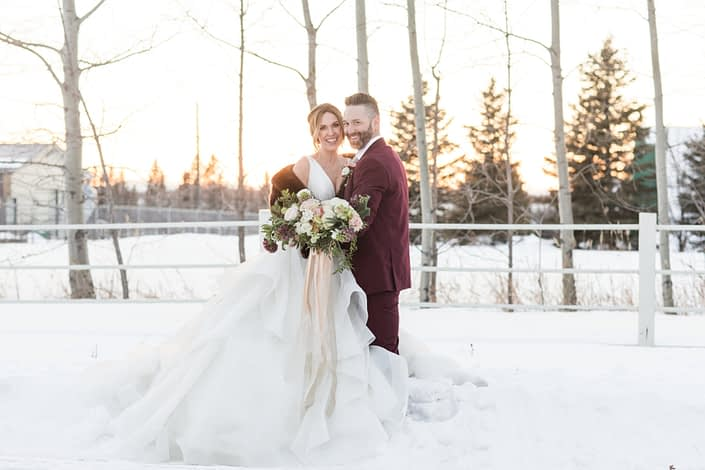 bride and groom in burgundy suit with bridal bouquet designed with burgundy frittilaria, hanoi ranunculus and ivory lisianthus