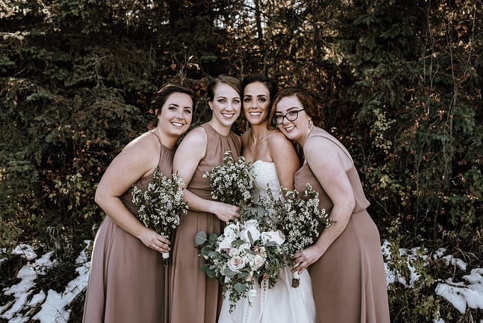 bride and bridesmaids in dusty rose dresses with wax flower bouquets