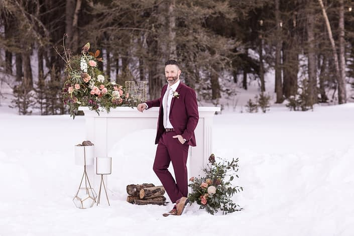 Winter weddig styled shoot with groom in burgudy suit and mantle floral arrangements in peach and burgundy