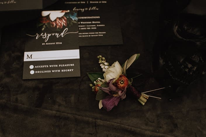 boutonniere close up with red ranunculus and purple clematis and white pieris and white anemone on velvet cloth with black invitation in background