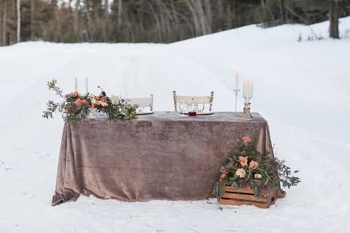 winter wedding sweetheart table with grey velvet linen and peach, blush and burgundy flowers