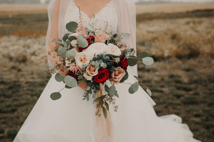 Loose and romantic blush bridal bouquet with pops of red roses and quicksand roses and white o'hara garden roses and pink astilbe and navy eryngium and mixed eucalyptus