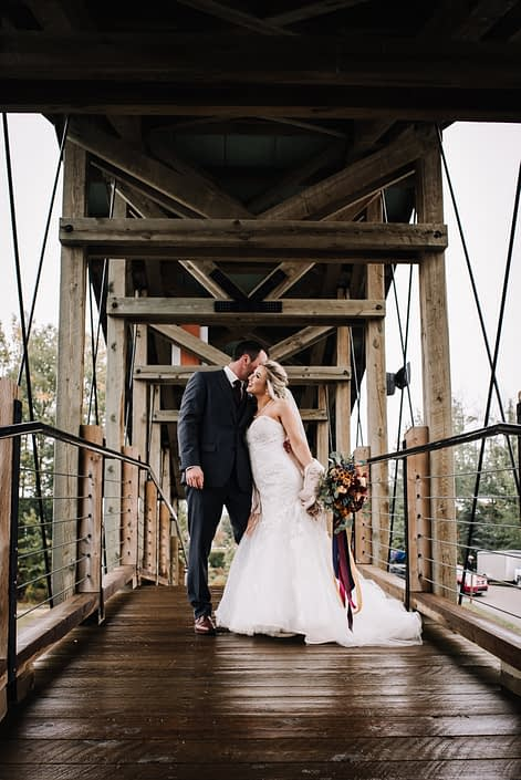 bride and groom on a rustic wooden bride in the autumn holding a bridal bouquet of burgundy, mustard yellow and orange
