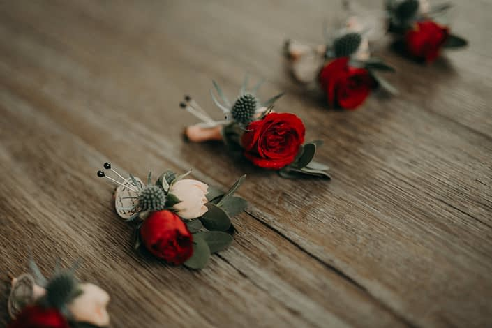 close up of boutonniere made with blush spray roses and red spray roses and eryngium and eucalyptus accent