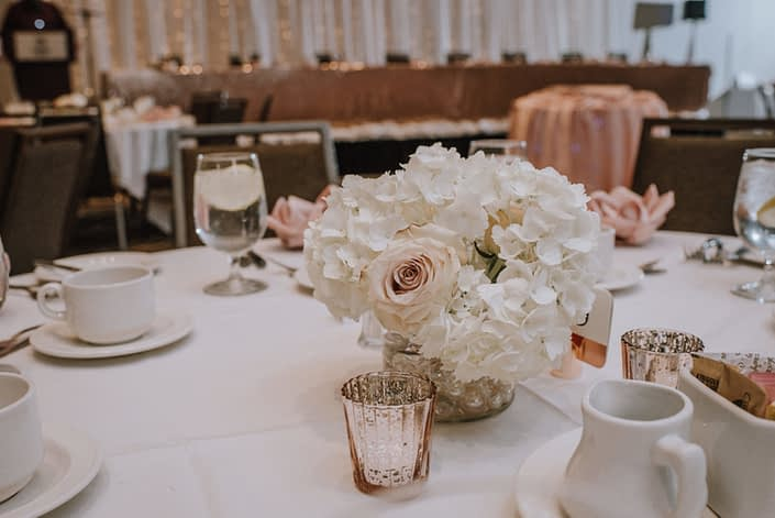 cambridge hotel wedding in red deer with white linens and centerpiece of white hydrangea and blush quicksand roses