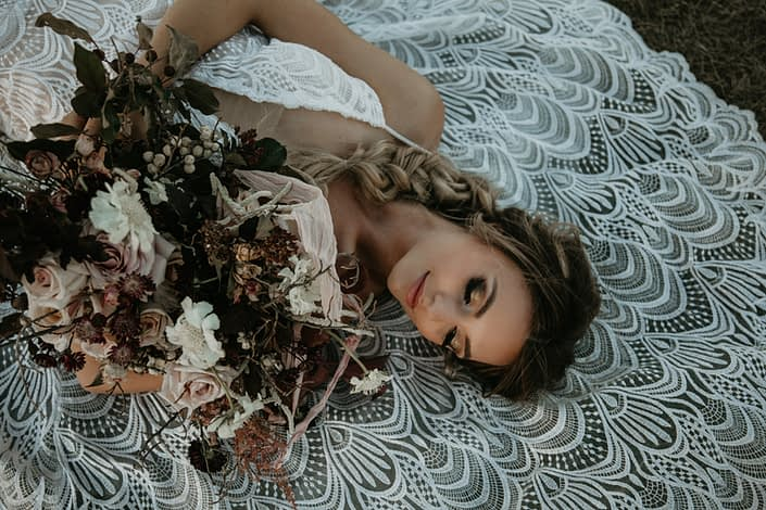 bride laying on lace dress with boho style braid in her hair and bridal bouquet of blush roses and burgundy leaves