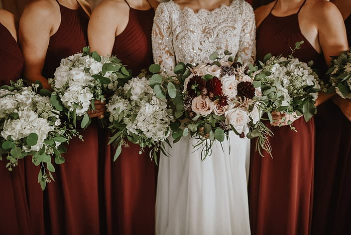 bride with bridal bouquet of blush and burgundy dahlia and roses and bridesmaids in burgundy holding bouquets of white hydrangea and astrantia and eucalyptus