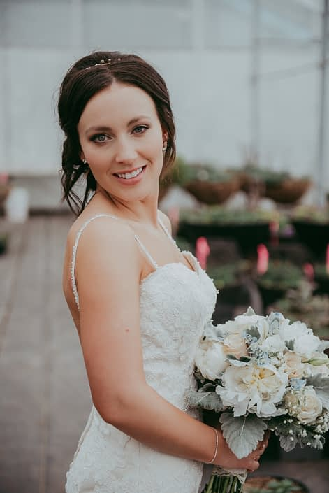 bride in a wedding dres holding a bouquet with white peonies, ivory roses, dusty miller and pale blue delphinium