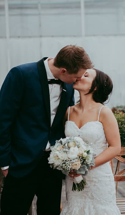 bride and groom kissing, holding a bouquet of white peony, ivory rose and dusty miller
