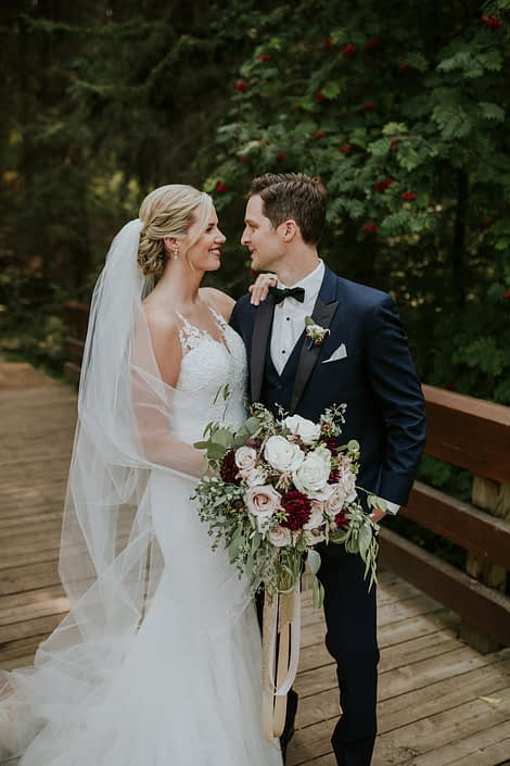 bride wearing a white wedding dress and cathedral veil with groom in navy tuxedo holding a bridal bouquet made with burgundy dahlia, white roses and blush roses and eucalyptus greenery