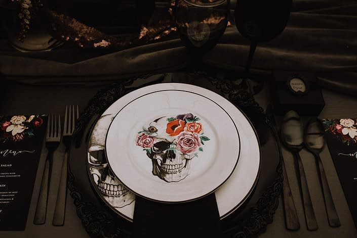 Alternative wedding table setting with skulls and floral plates and black flatware and black chargers and grey velvet runner
